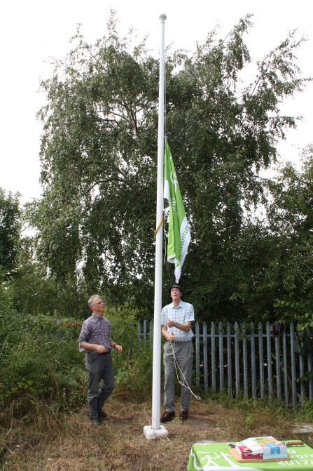 Green flag being raised at New Ferry Butterfly Park c. Richard Ash
